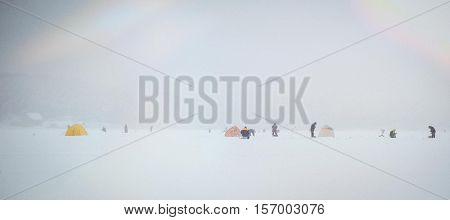 Frozen fishermen catch fish on a frozen lake