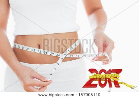 Midsection of woman measuring waist against digitally generated image of new year with tape measure