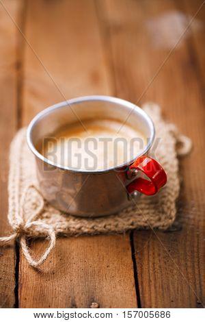 coffee in unusual vintage tin mug with red handle on old wood