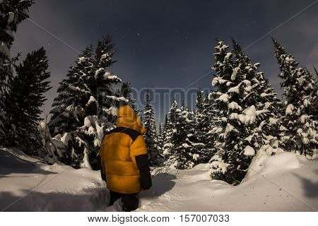 The man in the yellow jacket in winter forest among the trees in the snow.