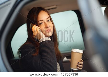 Portrait in car of business woman talking on phone with coffee take away in hand. Model looking at camera