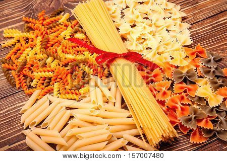 Spaghetti Tied With A Red Ribbon, A Number Of Different Types Of Pasta, Lying Around On Vintage Wood