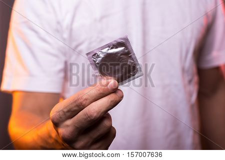 Unknown man in white shirt holding condom in hand closeup. Safety sex concept.