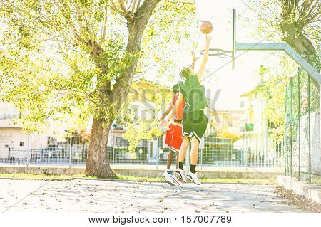 Young athletes in action outdoor with back light - Basketball player performing slam dunk on court in city urban grunge camp - Sport concept - Warm vintage filter with green sun flare in background