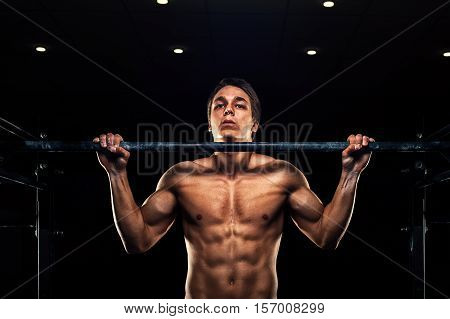 Young strong man doing pull ups exercise on horizontal bar. Fitness sports workout.