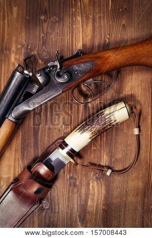 Hunting rifle and knife on the wooden background