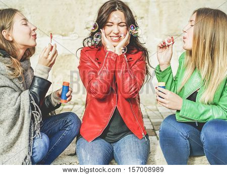 Young cheerful women having fun blowing soap bubbles outdoor - Best friends sharing free time in the old town in a sunny day - Girlfriends enjoying everyday life moments - Focus on middle girl