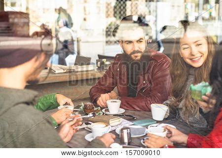Group of friends enjoying cappuccino and latte macchiato together in a coffee shop - View through glass with reflections - Caffeine addiction concept - Focus on bearded man - Warm vintage filter