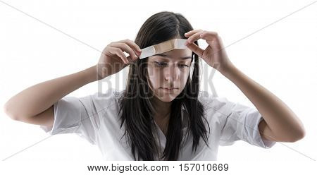 Teen girl applying herself adhesive bandage isolate on white background.