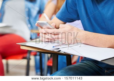 Student texting in class with his smartphone at school