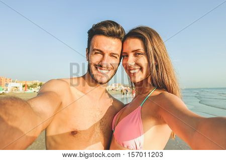 Happy traveling couple making selfie with beach in background - Concept of sunny summer colors and romantic mood - Young people laughing and making emotional faces outdoor - Warm soft vintage filter
