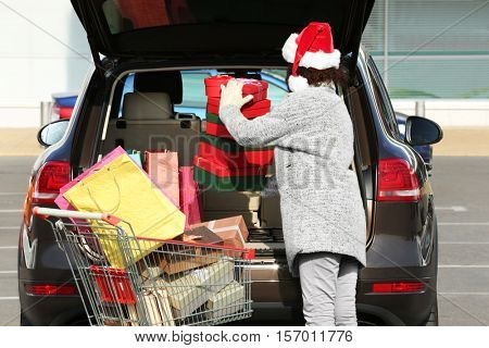 Woman putting gifts in car trunk outdoors