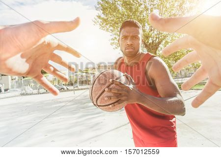Multiracial basket player playing a game in urban quarter street camp outdoor with back lighting- Athlete hands trying to catch the ball from his opponent - Sport concept - Focus on ball hands