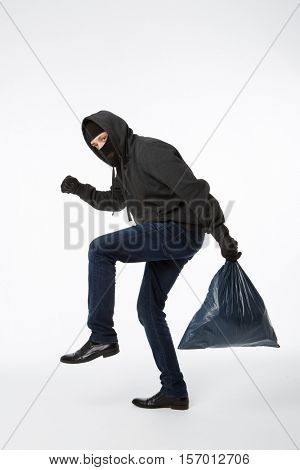 Thief slinking heavy blue bag