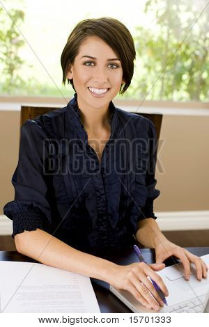 Friendly young business woman at her desk