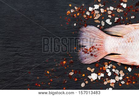 Tail of fresh raw red tilapia fish on black slate stone board with spices and pink himalayan salt. Culinary seafood background. Top view copy space