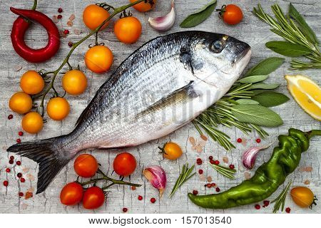 Fresh uncooked dorado or sea bream fish with lemon aromatic herbs vegetables and spices over grey stone background. Top view