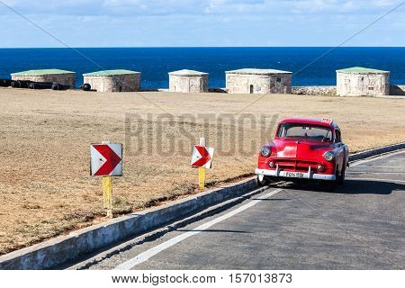 HAVANA, CUBA - January 25, 2016 Vintage convertible car is parked outside Castillo de la Real Fuerza waiting for passengers.