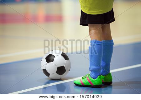 Football futbal training for children. Indoor soccer young player with a soccer ball in a sports hall. Player in yellow and blue uniform. Sport background.
