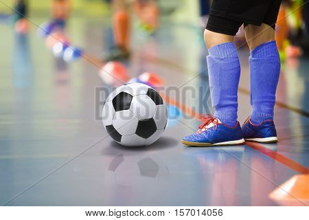 Children training soccer futbal indoor gym. Young boy with soccer ball training indoor football. Little player in dark blue sports socks
