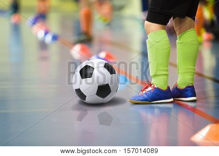 Children training soccer futbal indoor gym. Young boy with soccer ball training indoor football. Little player in light green sports socks