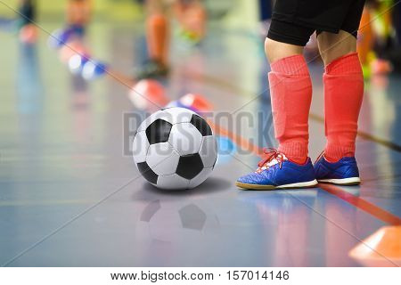 Children training soccer futbal indoor gym. Young boy with soccer ball training indoor football. Little player in light red sports socks