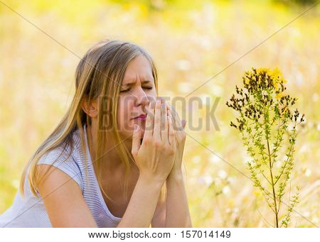 Woman with sad expression sneezing because of pollen allergy.