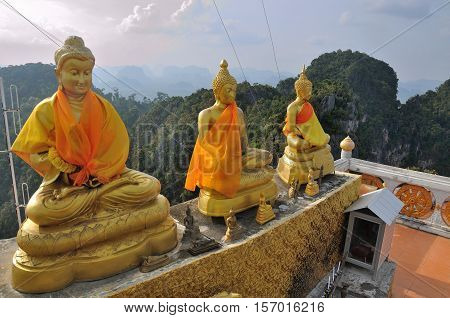 Tiger Cave Temple in Thailand, Krabi. Golden Buddha statues, located high above the mountain, after steep climb of 1237 stairs.