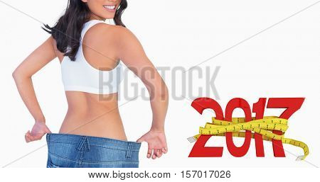 Woman holding her too big jeans smiling against digitally generated image of new year with tape measure
