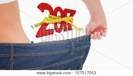 Close up of a woman waist in a too big pants against digital image of new year with tape measure