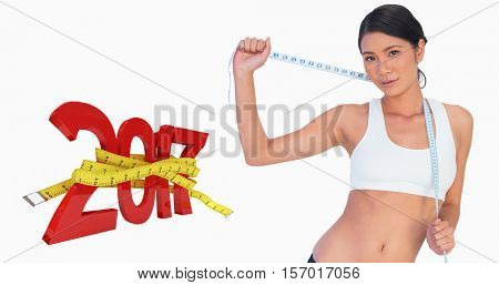 Self confident slim woman holding her measuring tape against digital image of new year with tape measure