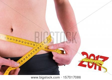 Slim woman measuring waist with tape measure against digitally generated image of new year with tape measure