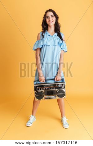 Full length portrait of a happy smiling brunette woman in blue dress listening music with boombox isolated on a orange background