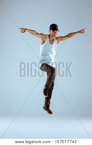 The man dancing fitness or hip hop choreography in gray studio background
