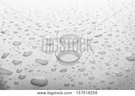 Pair of contact lenses and liquid drops on light background, close up view. Medicine and vision concept