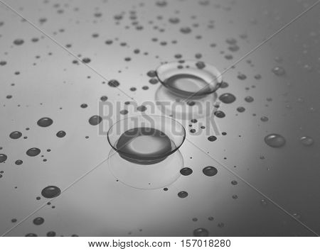 Pair of contact lenses and liquid drops on grey background, close up view. Medicine and vision concept