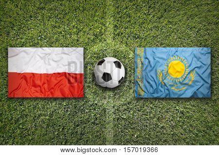 Poland vs. Kazakhstan flags on a green soccer field, 3d rendering