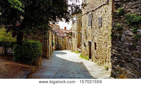 Old italian village in Tuscany. Pedestrian road between old buildings down the hill.