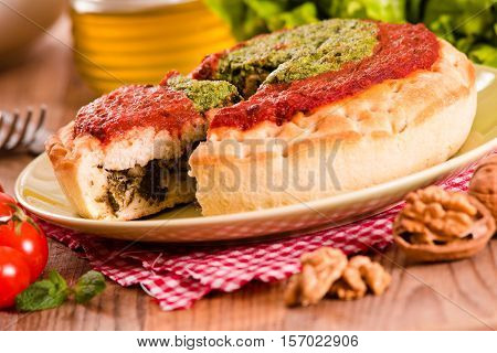 Calzone with walnuts and endive on white dish.