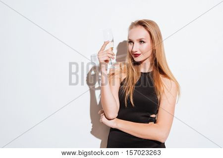 Smiling attrative young woman standing and drinking champagne over white background