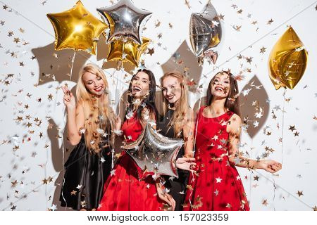 Four happy joyful young women with star shaped balloons and confetti having party over white background