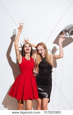 Two happy attractive yougn women drinking champagne and having party over white background