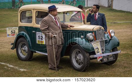 KOLKATA, INDIA - JANUARY 31, 2016: Proud owner stands beside his Austin Seven (1938 model) vintage car at the Statesman Vintage Car Rally at Fort William Kolkata.