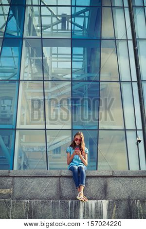 Young woman sitting outdoors and looking at her smart phone against business center