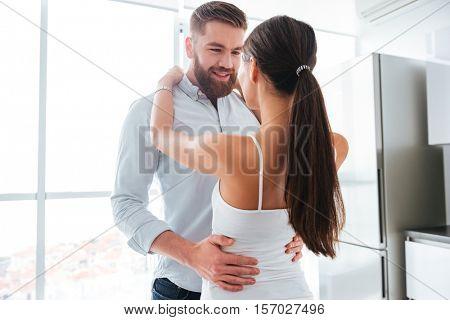 Cuddling couple in kitchen. eyes to eyes