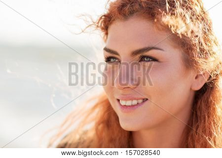 people, facial expression and emotion concept - close up of happy young redhead woman face