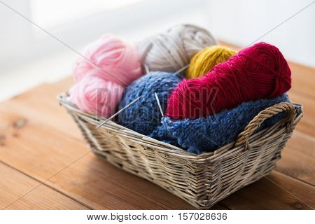 handicraft and needlework concept - wicker basket with knitting needles and balls of yarn