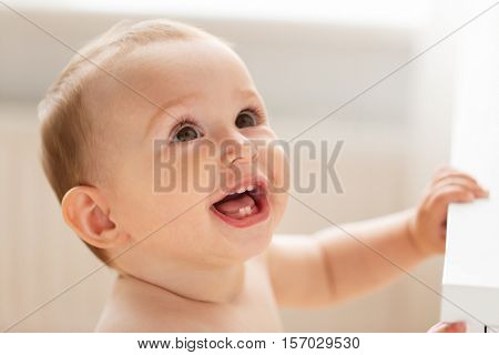 childhood, babyhood, emotions and people concept - close up of happy little baby boy or girl at home looking up
