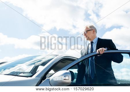 transport, business trip and people concept - senior businessman getting into car