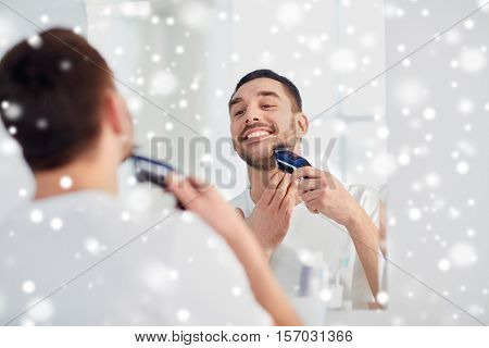 beauty, grooming, winter, christmas and people concept - young man looking to mirror and shaving beard with trimmer or electric shaver at home bathroom over snow